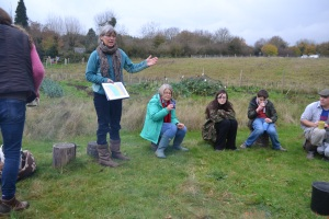Emily presenting plans to the group around the fire circle